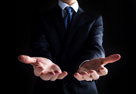Man in a business suit holding his hands out and showing something