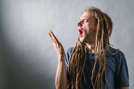Tired young man yawning on a solid background