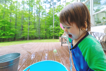 Young toddler boy playing with water outside Stock Photo