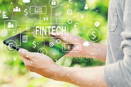 Fintech theme concept with man holding his tablet computer outside in the park
