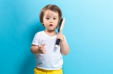Toddler boy with a hair brush on a blue background Stockfoto