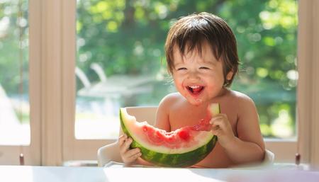 Gelukkige peuterjongen die watermeloen in zijn kinderstoel eet