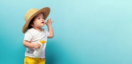 Niño pequeño con una botella de bloqueador solar sobre un fondo azul. Foto de archivo