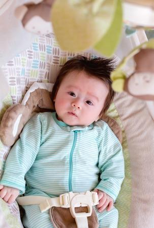 Newborn baby boy sitting in his rocking swing