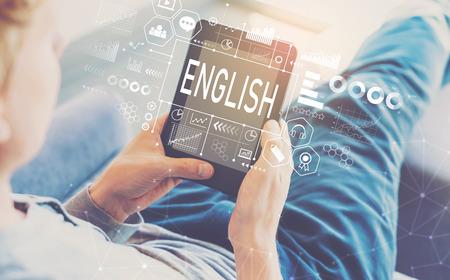 Englisch mit Mann, der eine Tablette in einem Stuhl benutzt Standard-Bild