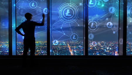 Litecoin with man writing on large windows high above a sprawling city at night Stock Photo