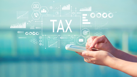 Tax with person holding a white smartphone Stock Photo