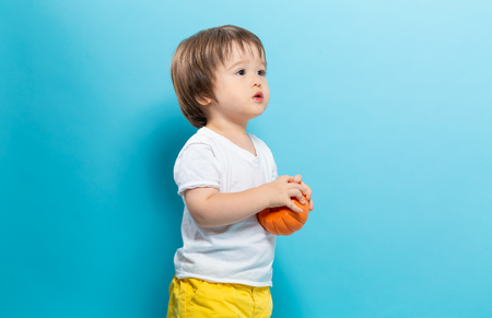 Toddler boy holding a pumpkin for halloween on a blue background Stock Photo