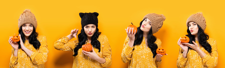 Young woman holding pumpkins for halloween on a yellow background