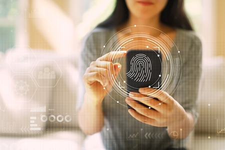 Fingerprint scanning technology with woman using her smartphone Stok Fotoğraf