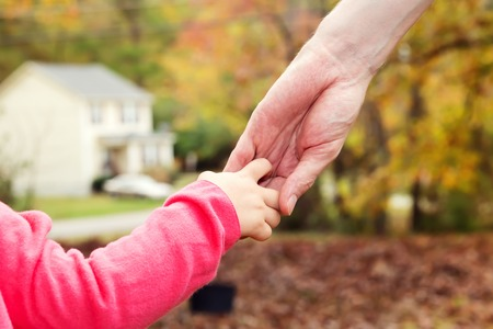 Toddler girl holding hands with her father outside on a fall day