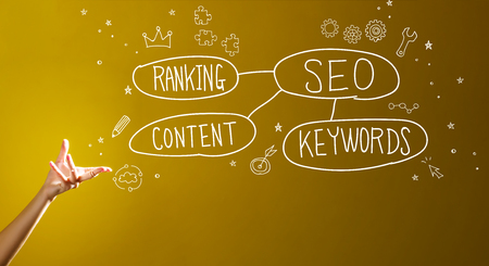 SEO concept with a hand in a dark yellow background