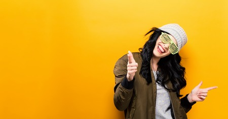 Fashionable and happy woman in a bomber jacket on a golden yellow background Stock Photo