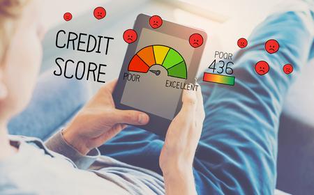 Schlechter Kredit-Score mit Mann, der eine Tablette in einem Stuhl benutzt