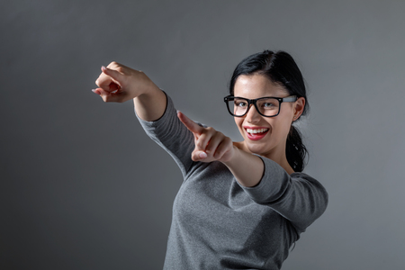 Young woman pointing at something on a solid background