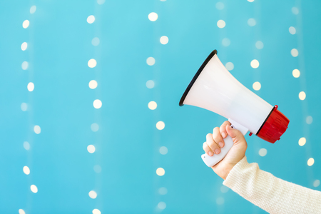 woman holding a megaphone on a shiny light blue background Stock Photo