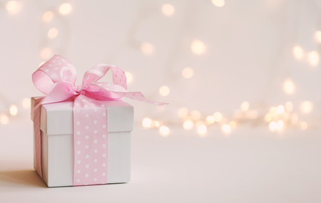 Eine Geschenkbox auf einem glänzenden hellen Hintergrund