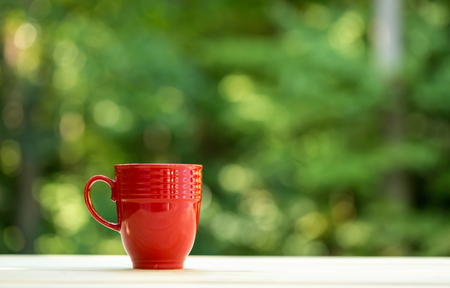 A coffee mug on a shiny green forest background