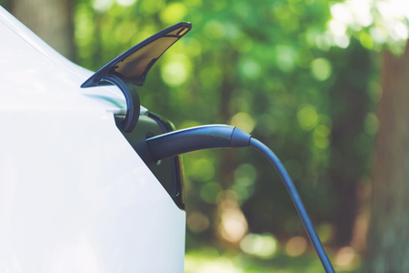 Charging an electric vehicle with a green forest background Stock Photo - 108122490