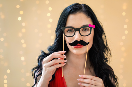 Young woman holding paper glasses and mustache party sticks on a shiny light background