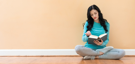 Young woman with a book against a big interior wall