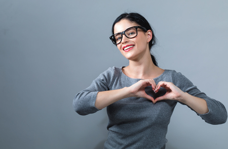 Woman making a heart shaped gesture with her hands