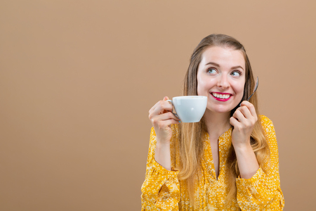 Young woman drinking coffee on a brown background