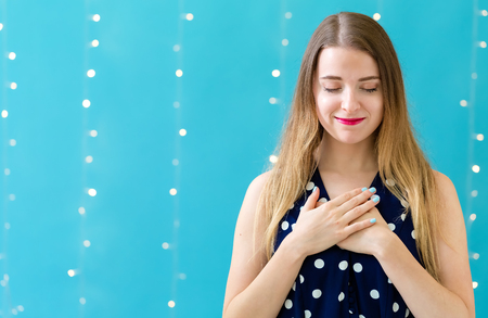 Woman with heartfelt expression on a shiny light background Stock Photo