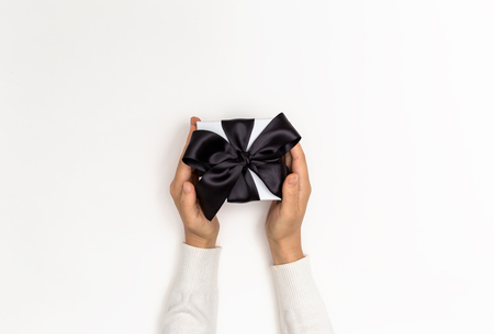 Woman holding a gift box on a white background