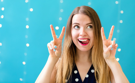 Young woman giving the peace sign on a shiny light background