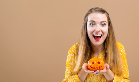Young woman holding a pumpkin for halloween on a brown background
