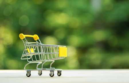 Little shopping cart on a shiny green forest background