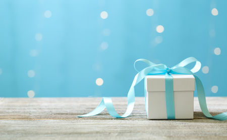 A gift box on a shiny light blue background