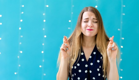 Young woman crossing her fingers and wishing for good luck on a shiny light background
