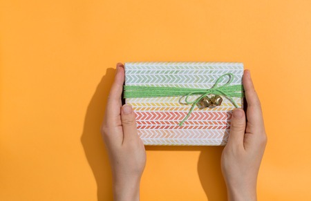 Woman holding a gift box on a orange background Stock Photo