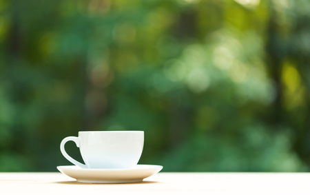 A coffee cup on a shiny green forest background