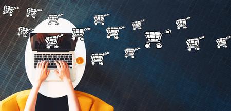 Compras en línea con la persona que usa una computadora portátil en una mesa blanca