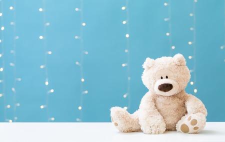 Een teddybeer op een glanzende lichtblauwe achtergrond
