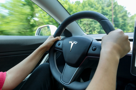 RALEIGH, NC - JUNE 08, 2018: Man driving an all electric Tesla Model 3. The Model 3 is set to be the Teslas first mass market electric vehicle. Stock Photo - 118178118