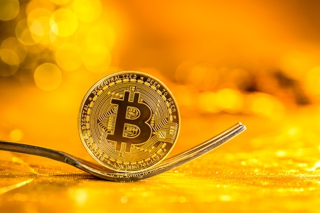 Bitcoin cryptocurreny fork concept on a shining gold background