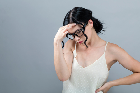 Young woman suffering from head ache on a solid background