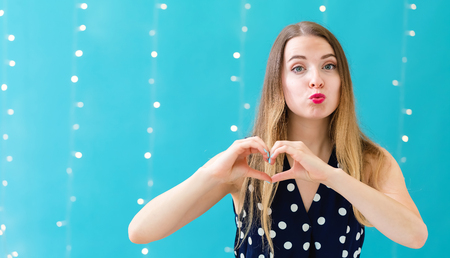 Woman making a heart shaped gesture with her hands on a shiny light background