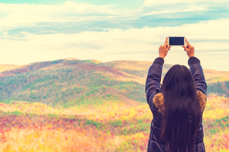 Woman taking a photo high above the mountains 스톡 콘텐츠