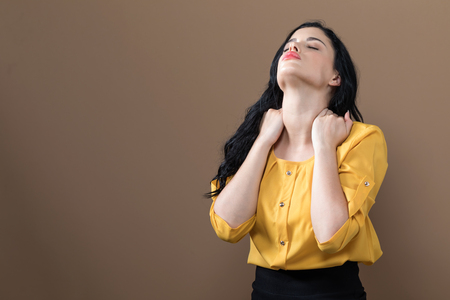 Young woman suffering from neck pain on a solid background Reklamní fotografie