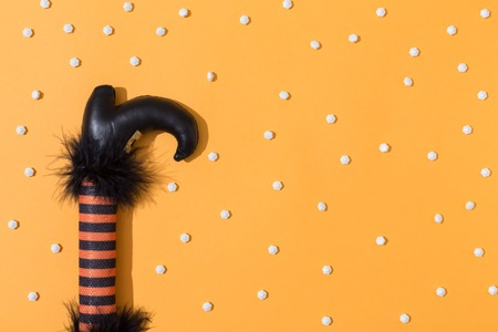 Halloween theme with witches leg decoration on a orange background