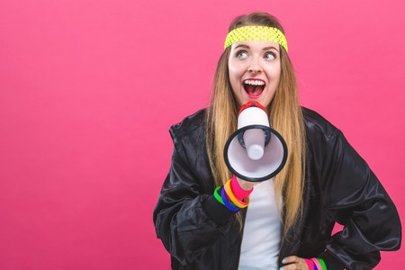 Woman in 1980s fashion holding a megaphone on a pink background Stock Photo