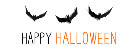 Happy Halloween message with paper bats overhead view on a solid color