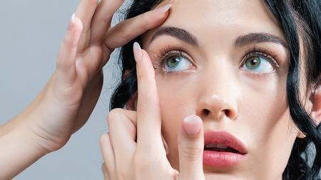 Mujer joven con lentes de contacto sobre un fondo gris