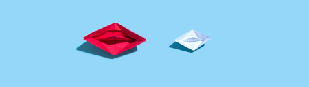 Two paper boats on a blue background