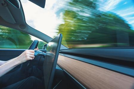 Veicolo di lusso che guida lungo la strada con sfocatura di movimento